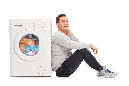 machine man: Young man sitting next to a washing machine and waiting for the laundry isolated on white background