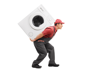 machine man: Studio shot of a young worker carrying a washing machine on his back isolated on white background