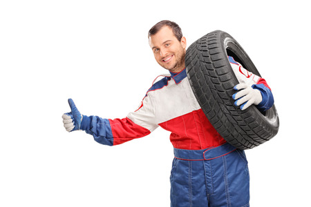 shoulder carrying: Young car racer carrying a tire on his shoulder and hitchhiking with his thumb isolated on white background