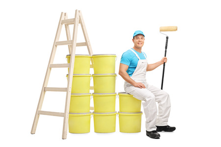decorator: Young male decorator sitting on a pile of color buckets next to a wooden ladder isolated on white background
