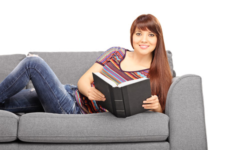 Caucasian woman: Relaxed young girl lying on a gray sofa and holding a book isolated on white background