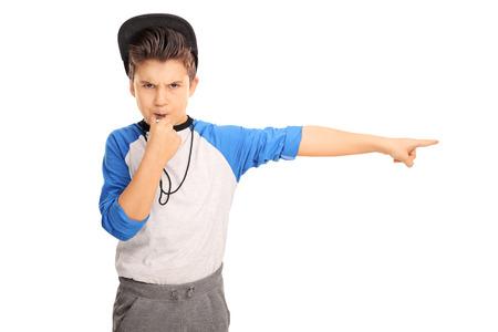 Estudio foto de un niño enojado en ropa deportiva que sopla un silbato y señala a la derecha aislado en fondo blanco