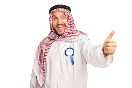 posing  agree: Young cheerful Arab with a blue award ribbon on his robe giving a thumb up isolated on white background