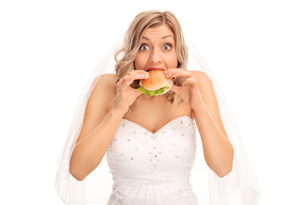 unhealthy: Surprised blond bride eating a sandwich and looking at the camera isolated on white background Stock Photo