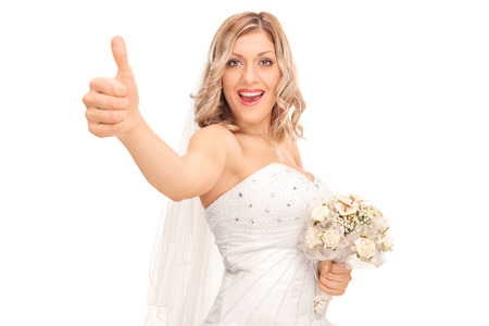 posing  agree: Joyful young bride holding a wedding bouquet and giving a thumb up isolated on white background Stock Photo