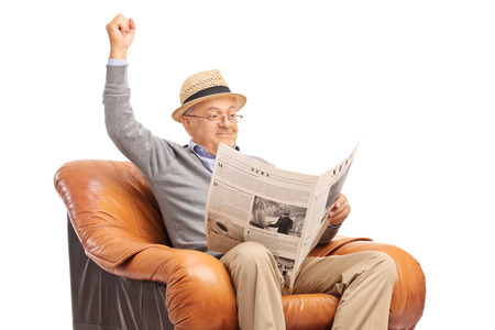 fist: Senior gentleman reading the news and celebrating with his fist in the air isolated on white background