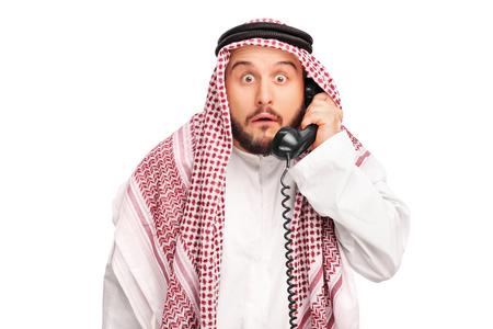 sorprendido: Sorprendido Árabe sostiene un altavoz del teléfono y mirando a la cámara aislada en el fondo blanco Foto de archivo