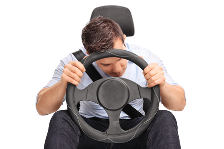 irresponsible: Studio shot of a young driver sleeping while driving isolated on white background