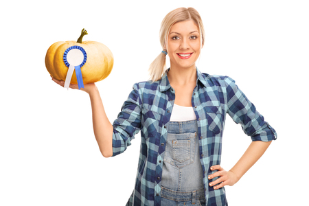it is isolated: Young woman holding a pumpkin with a blue award ribbon on it isolated on white background Stock Photo
