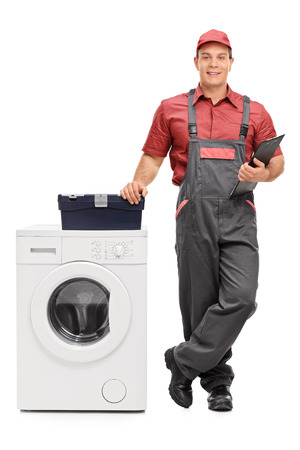 クリップボードに保持、白い背景で隔離の洗濯機の横に立っている若い男性修理の完全な長さの肖像画