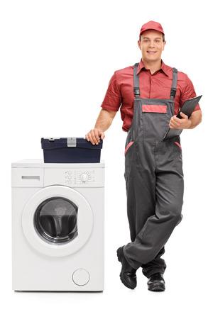 Retrato de cuerpo entero de un reparador varón joven que sostiene un sujetapapeles y de pie junto a una lavadora aislada en el fondo blanco