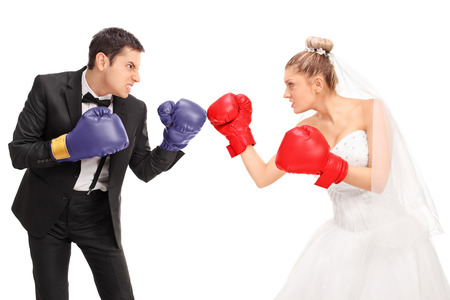 Young bride and groom with boxing gloves fighting each other isolated on white background