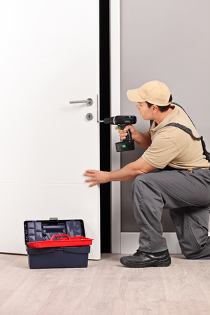 Vertical shot of a young male locksmith installing a door lock with an electric hand drill Stockfoto