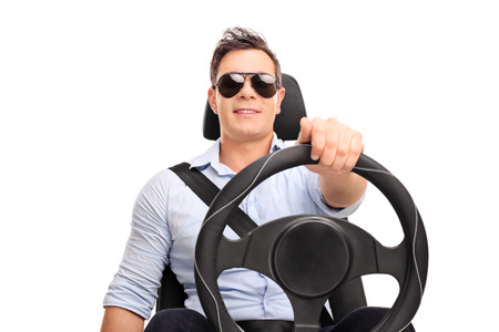 Atelieraufnahme eines jungen Mannes, der ein Lenkrad hält und vortäuscht zu fahren lokalisiert auf weißem Hintergrund