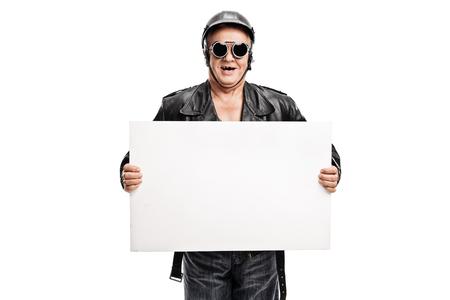 oldschool: Studio shot of an old-school senior biker holding a white banner isolated on white background Stock Photo