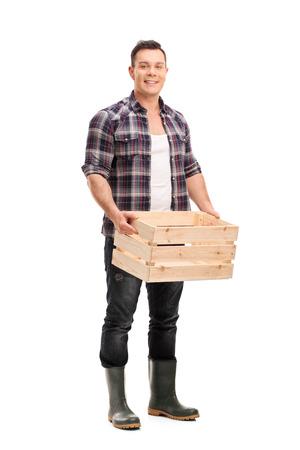 Full length portret van een jonge mannelijke boer die een lege houten kist houdt en naar de camera kijkt die op een witte achtergrond wordt geïsoleerd Stockfoto