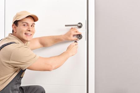 Fröhlich Schlosser ein Türschloss an einem neuen weißen Tür Installation und schaut in die Kamera