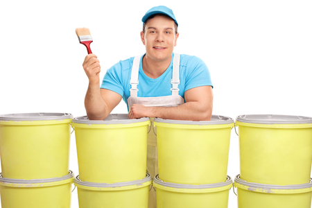 decorator: Young male decorator holding a paintbrush and posing behind a stack of color buckets isolated on white background Stock Photo