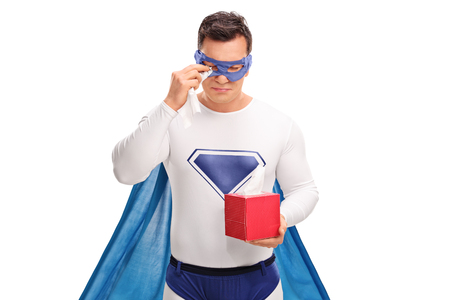 whining: Sad superhero holding a box of wipes and crying isolated on white background