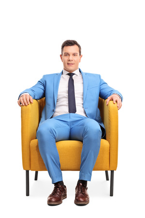 white suit: Vertical shot of a young man in an elegant blue suit sitting in an armchair isolated on white background