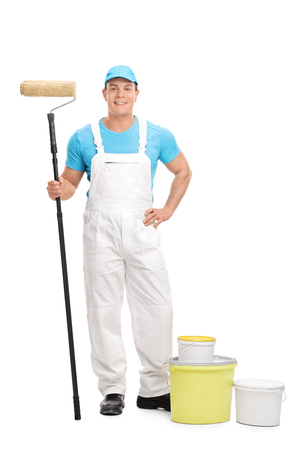 decorator: Full length portrait of a young male decorator holding a paint roller and looking at the camera isolated on white background