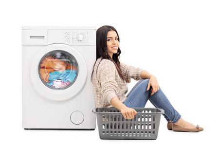 Mujer joven que espera la ropa sentado al lado de una lavadora aislada en el fondo blanco