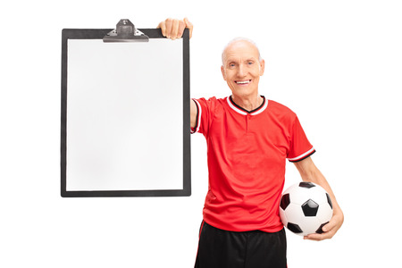 soccer coach: Senior soccer coach holding a ball and a clipboard with a blank sheet on it isolated on white background Stock Photo
