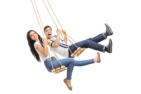 Young cheerful man and woman swinging on wooden swings isolated on white background