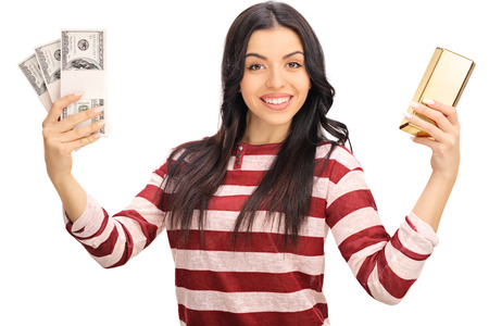 gold bar: Studio shot of a joyful woman holding a few stacks of money and a gold bar isolated on white background Stock Photo