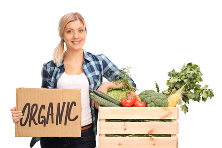 single person: Female agricultural worker holding a cardboard sign that says organic and leaning on a crate full of vegetables isolated on white background