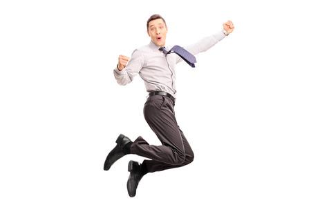 祝賀会: うれしそうな青年実業家ジャンプと幸福の白い背景に分離されて空中でショットを身振りで示すこと