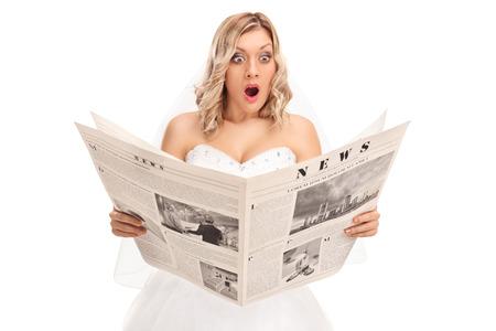 白い背景に分離された新聞を読んで驚いた若い花嫁のスタジオ撮影 写真素材