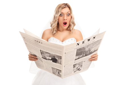 Studio shot of a surprised young bride reading a newspaper isolated on white background Stock Photo