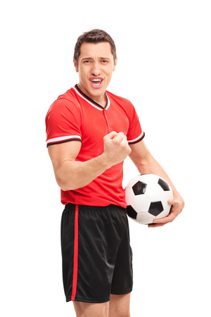 young guy: Vertical shot of a happy football player holding a ball and looking at the camera isolated on white background