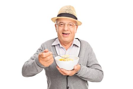 comiendo cereal: Studio foto de una mayor alegre caballero comer cereal de un recipiente aislado en el fondo blanco Foto de archivo