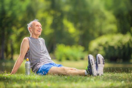 escucha activa: El hombre mayor activo en ropa deportiva sentado en el parque y escuchar m�sica en los auriculares dispar� con inclinaci�n y desplazamiento de la lente