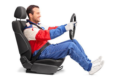 Profile shot of a young car racer holding a steering wheel and pretending to drive isolated on white background Stock Photo