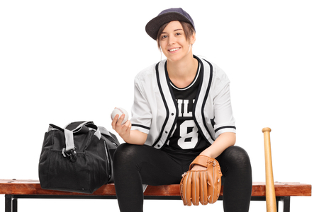 player bench: Young female baseball player seated on a wooden bench and looking at the camera isolated on white background