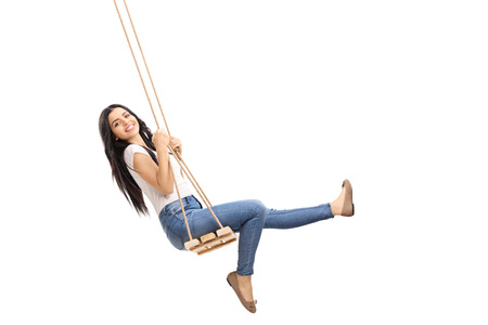 columpios: chica despreocupada joven balanceándose en un columpio de madera y mirando a la cámara aislada en el fondo blanco Foto de archivo