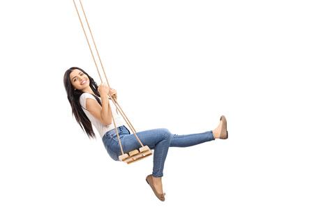 Jong onbezorgd meisje swingende op een houten schommel en kijken naar de camera op een witte achtergrond