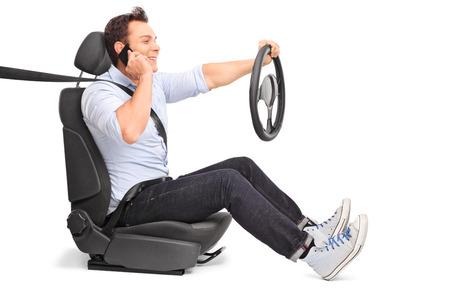 hablando por telefono: Hombre joven que conduce y que habla en su teléfono celular aislado en el fondo blanco
