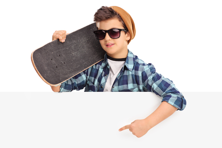 white poster: Cool kid holding a skateboard and pointing on a blank panel with his hand isolated on white background Stock Photo