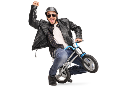 Joyful biker riding a small childish bicycle and gesturing with his hand isolated on white background Stock Photo