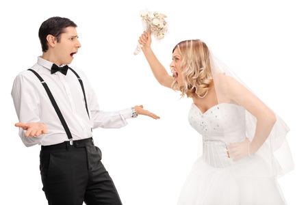 Studio, coup, une jeune mariée crier à l'époux et menaçant de lui isolé sur fond blanc Banque d'images