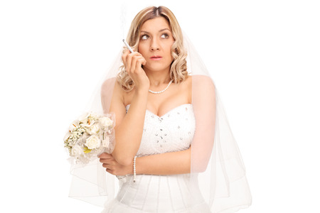 uptight: Young nervous bride in a white wedding dress holding a bouquet and smoking a cigarette isolated on white background