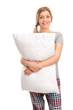 mujer sola: Tiro vertical de una mujer rubia alegre abrazando una almohada y mirando a la cámara aislada en el fondo blanco