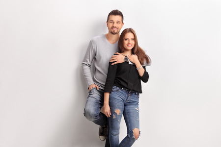 leaning: Young couple leaning against a white wall and looking at the camera