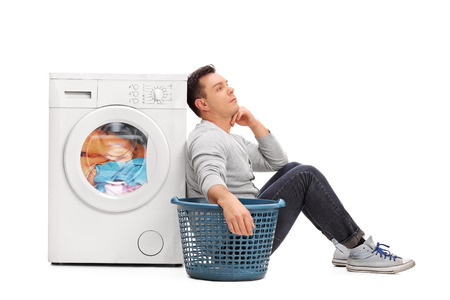 machine man: Bored young man sitting by a washing machine and waiting for the laundry isolated on white background