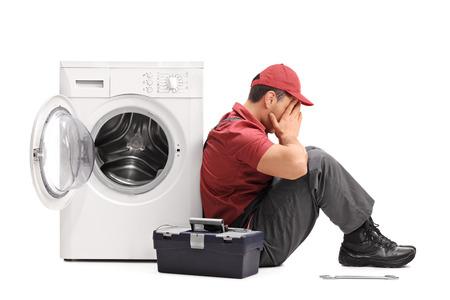 decepcionado: Studio foto de una joven reparador decepcionante que se sienta por una lavadora rota aislada en el fondo blanco