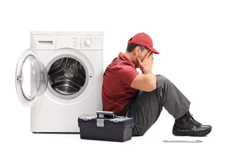 disappointed: Studio shot of a disappointed young repairman sitting by a broken washing machine isolated on white background